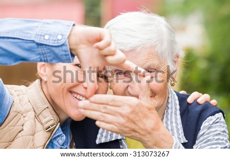 Photo of elderly woman with grandchild having funny