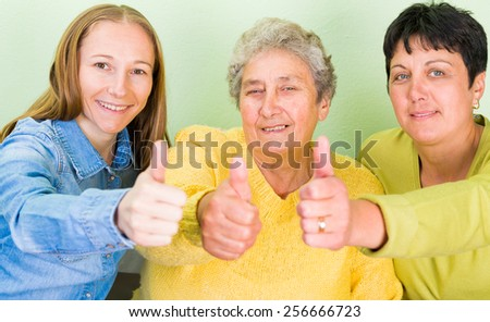 Photo of elderly woman with her daughters showing thumbs up