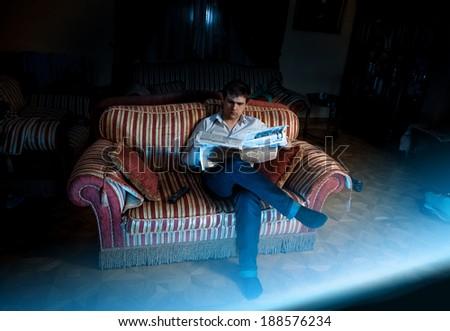 Photo of elegant man watching television on sofa at night - stock photo