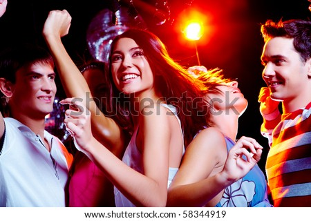 Photo of energetic girl dancing in the night club with her friends on background