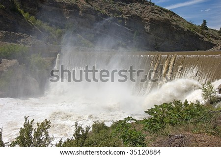 Photo of Enslow Dam in Washington state with desert type mountain, the muddy river going over the fall and mist rising up.