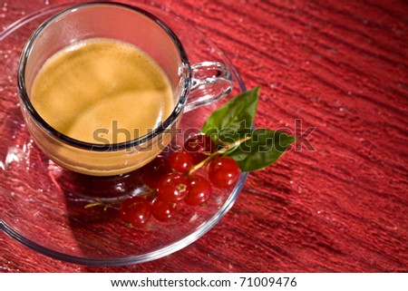 photo of espresso coffee with currants on red glasstable