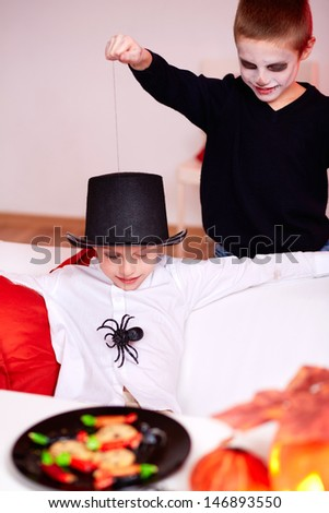 Photo of evil boy scaring his twin brother with spider on Halloween - stock photo