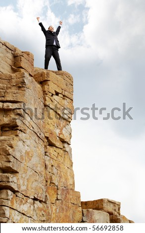 Photo of excited business man standing on the mountain with raised arms - stock photo
