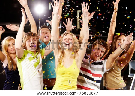 Photo of excited teenagers raising their arms in joy