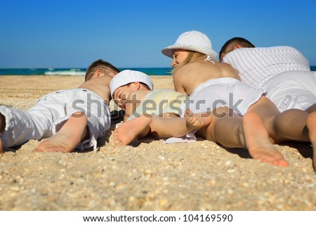 Photo of  family lying on sand on background of blue sky - stock photo