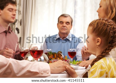 Photo of family members praying at festive table while holding each other by hands - stock photo