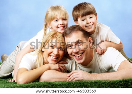Photo of family members smiling at camera on blue background