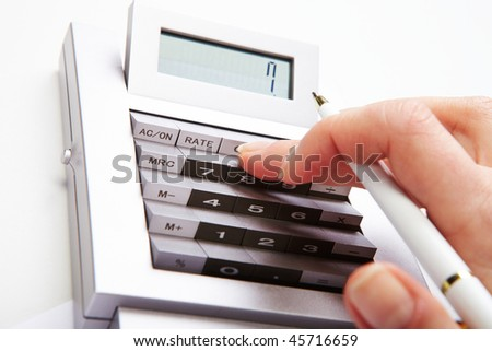 Photo of female hand with pen over calculator keys pushing them during work