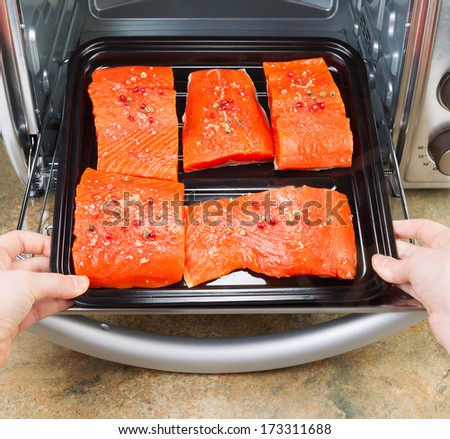 Photo of female hands placing fresh pieces of Wild Red Salmon into oven rack with stone counter top underneath - stock photo