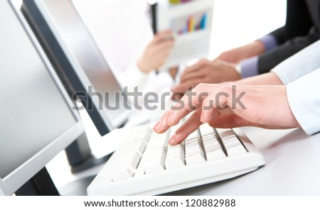 Photo of female hands typing on computer keyboard in working environment - stock photo