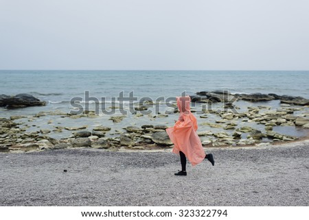 Photo of female runner in movement. Running girl on the sea coast. Misty and rainy day is the best time for morning jogging. Sport and active lifestyle helps us to stay always fit Workout training - stock photo