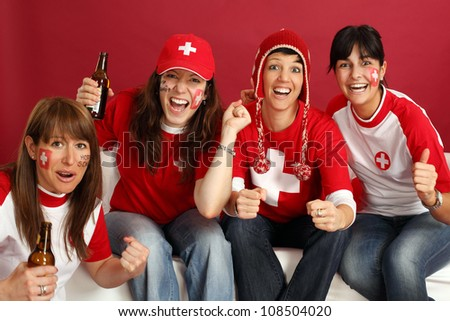 Photo of female Swiss sports fans smiling and cheering for their team. - stock photo