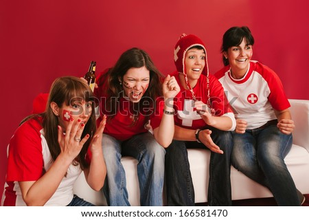 Photo of female Swiss sports fans watching television and cheering for their team.  - stock photo