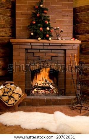 Photo of fireplace with firewood and warm white fur near by - stock photo