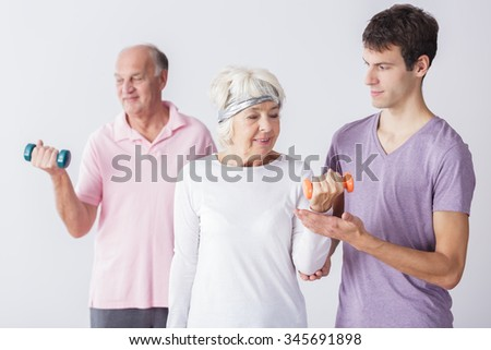 Photo of fitness seniors exercising at gym with trainer
