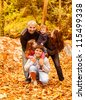 Photo of five happy person have fun outdoors, beautiful young parents play with two little children and adult son in autumnal backyard, happy family enjoying autumn nature, love concept - stock photo