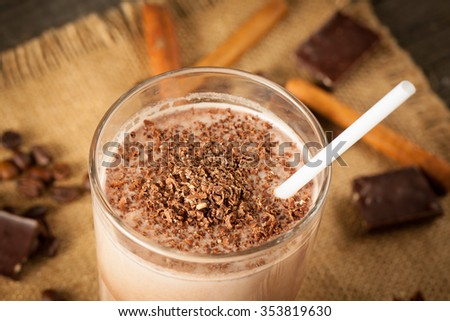 Photo of fresh Made Chocolate Banana Smoothie on a wooden table with coffee and spices. Selective focus. Milkshake. Protein diet. Healthy food concept. Drink, coffee beans, chocolate, cinnamon, anise. - stock photo