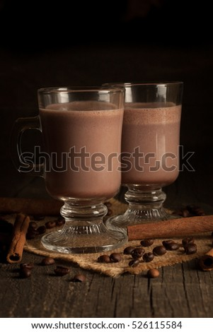 Photo of fresh Made Chocolate Banana Smoothie on a wooden table with coffee and spices. Selective focus. Milkshake. Protein diet. Healthy food and hot drink concept. Drink, coffee