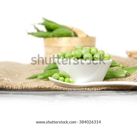 Photo of fresh peas and pods in a bowl and spoon on white background - stock photo