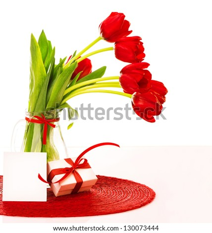 Photo of fresh red tulips bouquet in glass vase with blank card, greeting postcard, romantic bunch of spring flower, springtime holiday, happy mothers day, white gift box with red bow, love concept - stock photo