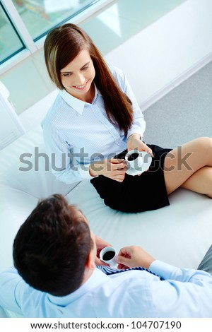 Photo of friendly business partners talking while drinking coffee in office - stock photo