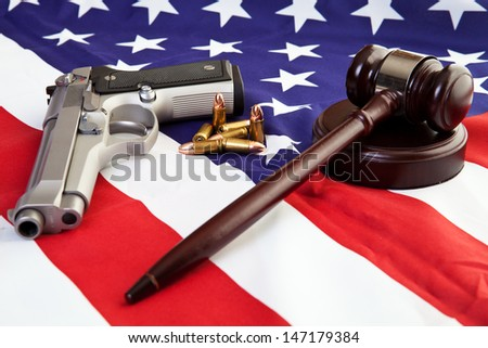 Photo of gavel, gun, and bullets over an american flag. - stock photo