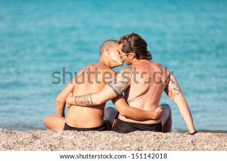 Photo of gay couple kissing in front of the beach - stock photo
