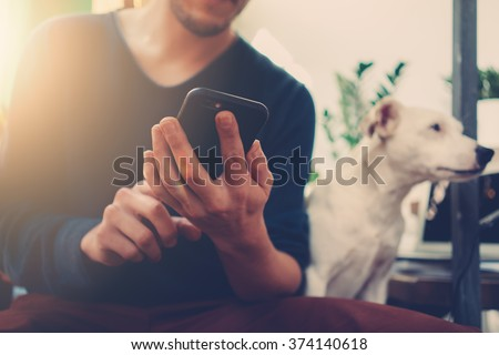 Photo of generic design smart phone holding in man hands for texting message. Blurred background - stock photo