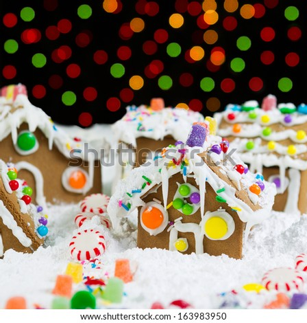 Photo of Gingerbread houses, surrounded by powdered snow, with colorful lights in background on black