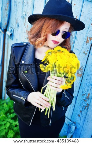 photo of girl in a black jacket and hat with a bouquet of dandelions
