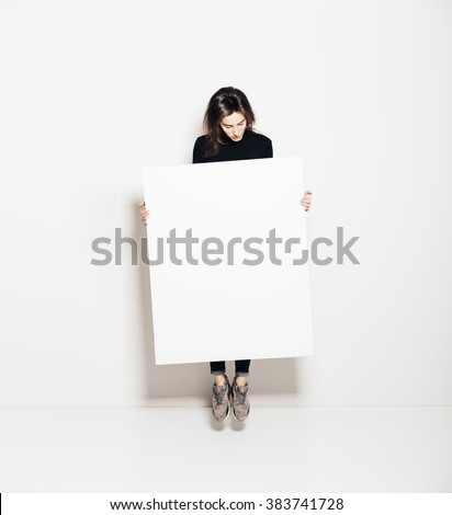 Photo of girl jumping in modern gallery and looking at the blank white canvas. Horizontal, mockup - stock photo