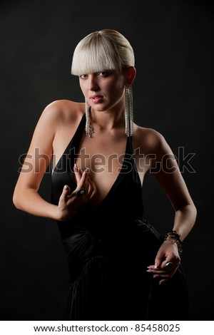 Photo of glamour model in an elegant black dress and beautiful jewelry posing in studio