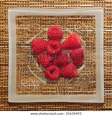 Photo of glass saucer with fresh and juicy raspberry - stock photo