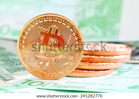 photo of golden bitcoins (new virtual currency) with traditional dollars and euro as a background . - stock photo