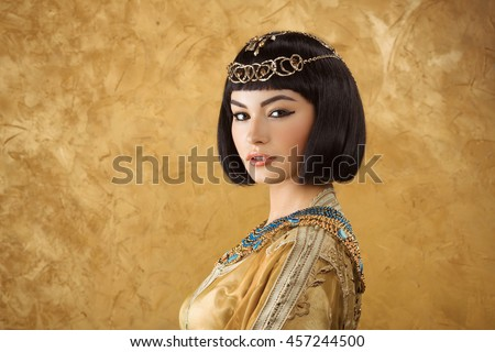 Photo of gorgeous woman with Cleopatra makeup, closeup portrait of beautiful female with stylish haircut agaist golden background, young lady wearing fashionable golden necklace, beauty salon - stock photo