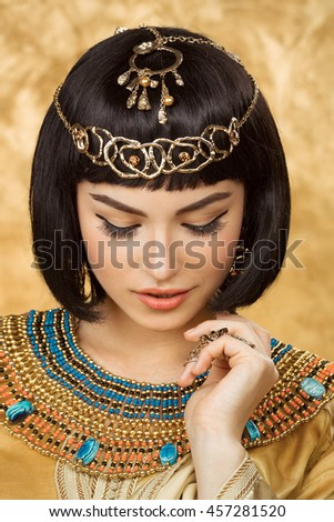 Photo of gorgeous woman with Cleopatra makeup, closeup portrait of beautiful female with stylish haircut on golden background, young lady wearing fashionable golden necklace, beauty salon