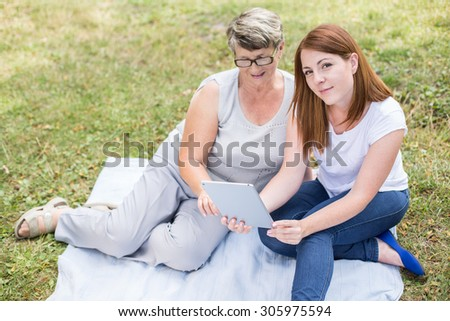 Photo of grandmother learning how to use tablet  - stock photo