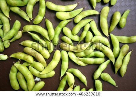 Photo of green beans in pods on brown background. String beans on a table. Organic products. Organic vegetables. Green vegetables. Fresh beans. - stock photo