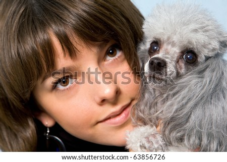 Photo of grey poodle with its master in studio