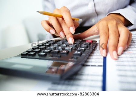 Photo of hands holding pencil and pressing calculator buttons over documents - stock photo