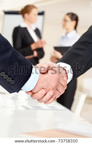 Photo of handshake of business partners after striking deal on background of communicating women - stock photo