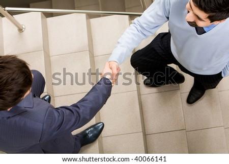 Photo of handshake of businessmen on staircase - stock photo