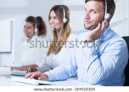 Photo of handsome consultant with computer in telesales center - stock photo