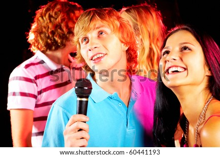 Photo of handsome guy singing at party with happy girlfriend near by