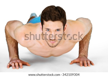 Photo of handsome muscular athlete on white background. Young man wearing sports shorts while training
