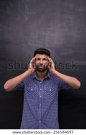 Photo of handsome young casual man on blank chalkboard background. Terrified man with headache