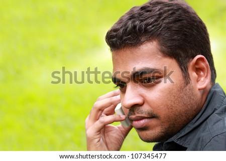 Photo of handsome young indian/south asian businessman talking and listening on cell phone with copy space for text.