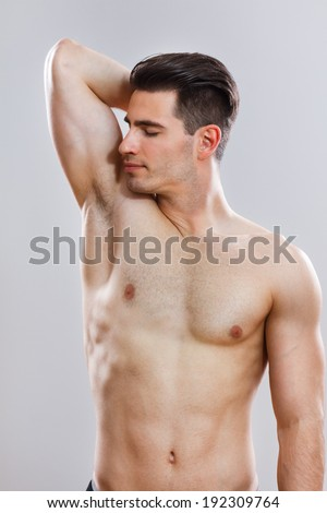Photo of handsome young man smelling his armpit after shower,Freshness after shower - stock photo