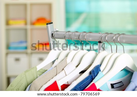 Photo of hangers with different clothes in department - stock photo